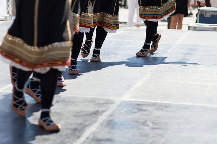 Low section of female dancers on walkway during traditional festival