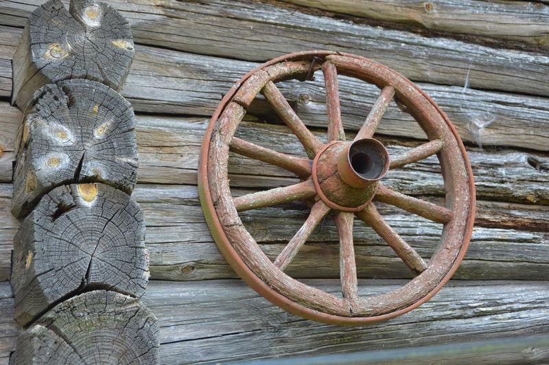 Low angle view of rusty wheel on log cabin
