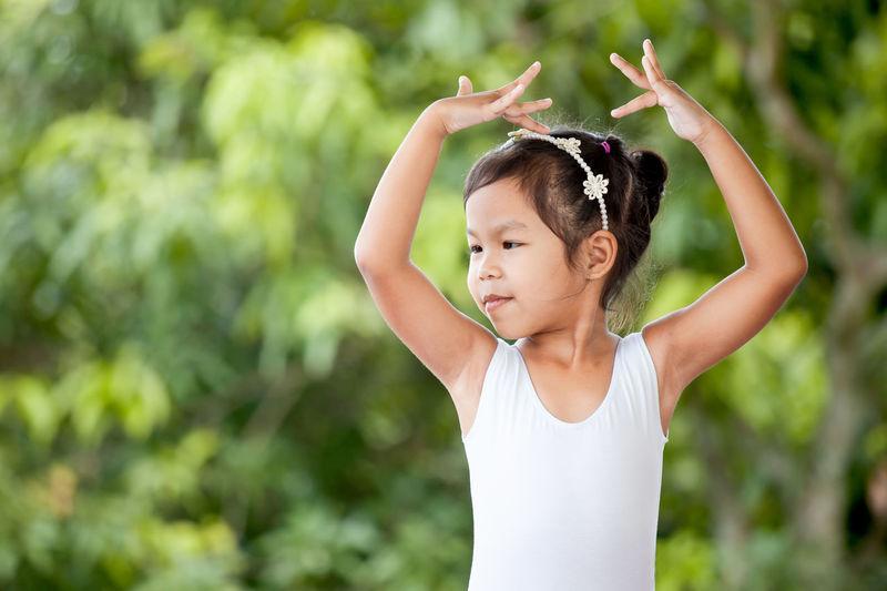 Cute girl dancing against plants