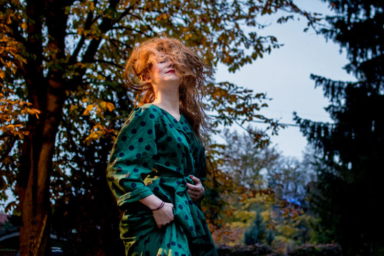 Portrait of young woman with tousled hair standing against trees