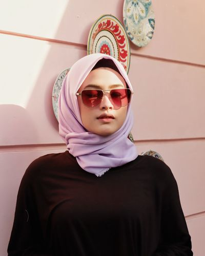 Young woman wearing sunglasses and headscarf against wall