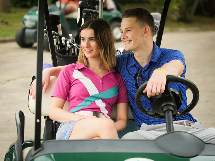 Young Couple Sitting On Golf Cart