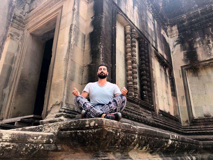 Full length of man sitting at historic building