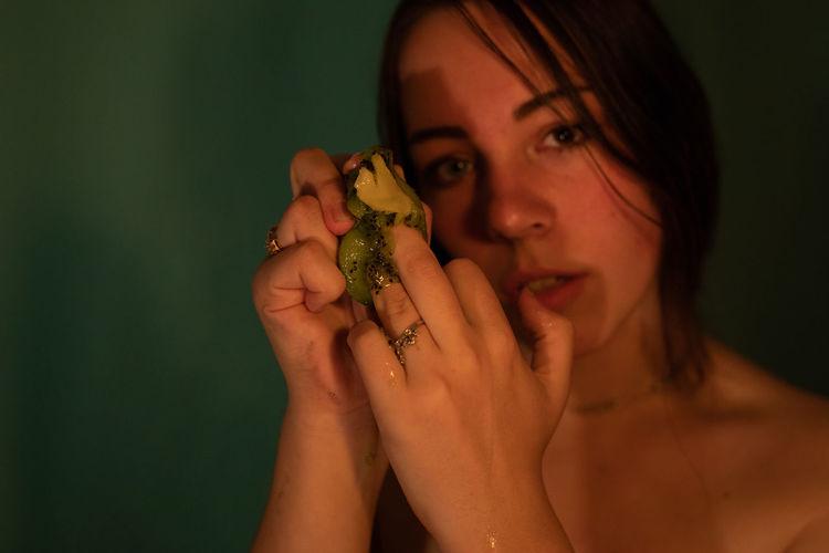 Close-up portrait of woman holding kiwi