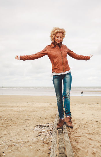 Smiling Mid Adult Woman Walking On Wood At Beach