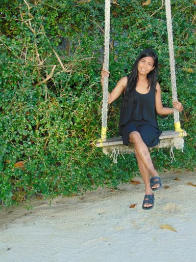 Full length portrait of young woman sitting on swing against plants