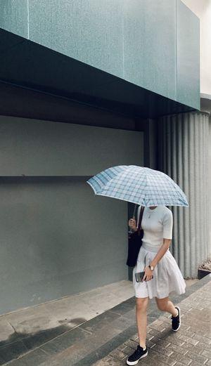 Full length of woman holding umbrella walking on street