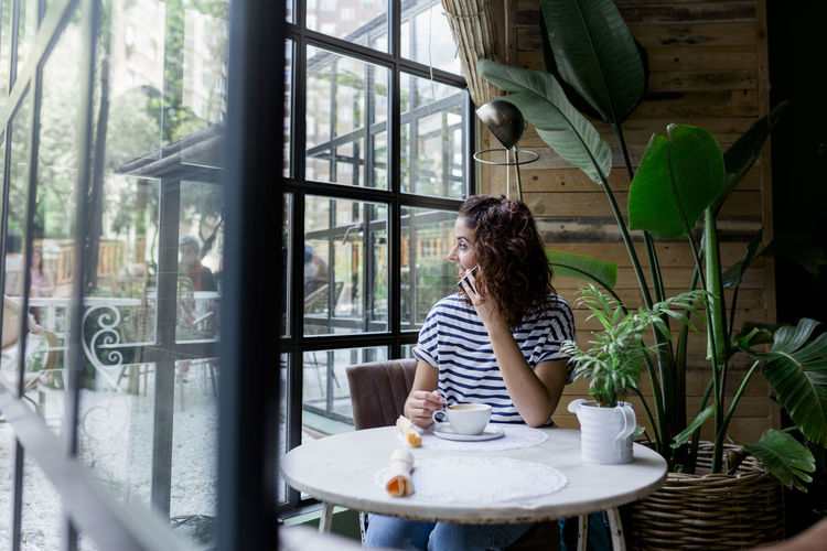 Woman looking through window while talking on mobile phone at cafe
