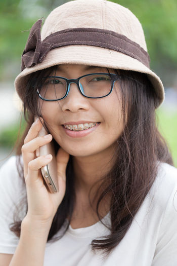 Close-up portrait of smiling young woman talking on phone