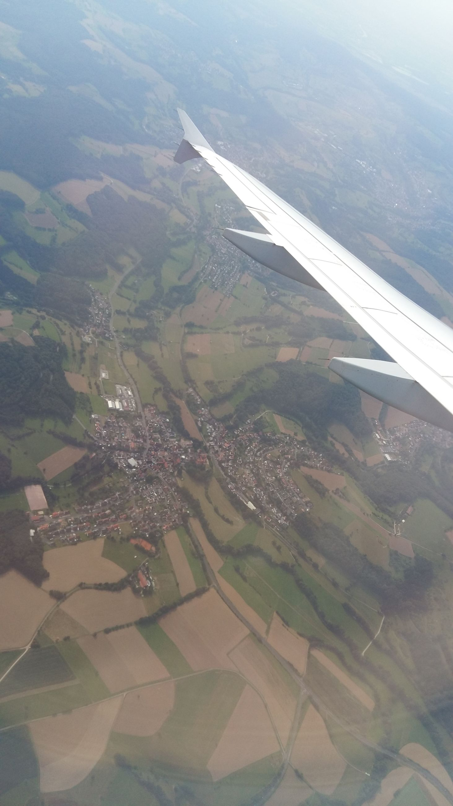 landscape, aerial view, airplane, transportation, aircraft wing, water, scenics, flying, mode of transport, tranquil scene, tranquility, beauty in nature, rural scene, travel, air vehicle, sea, nature, idyllic, agriculture, journey, mountain, day, field, coastline, outdoors, farm, patchwork landscape, cultivated land, distant, wide shot, non-urban scene, airplane wing