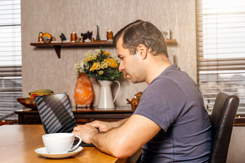 Side view of man holding coffee cup on table