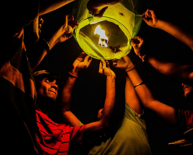 Low Angle View Of Friends Holding Illuminated Paper Lantern At Night