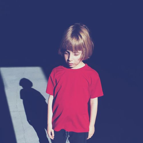 Boy standing against blue background