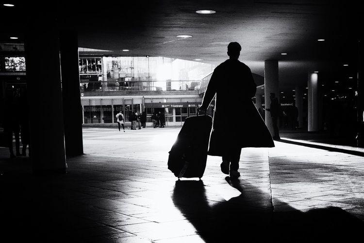 Rear view of silhouette man walking on illuminated walkway