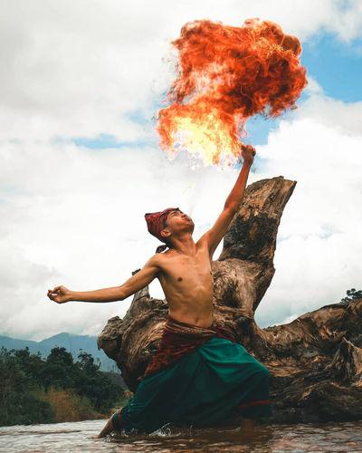Full length of shirtless man dancing against sky