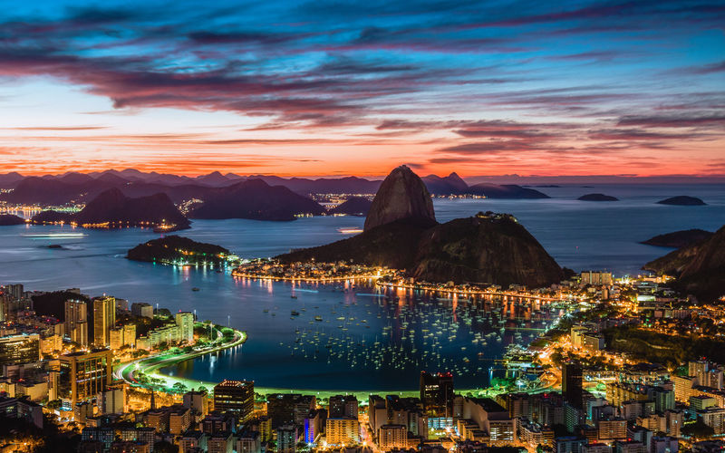 Illuminated city by sea against sky at sunset