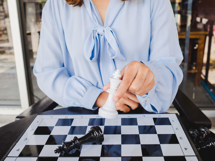 Midsection of woman playing on chess board