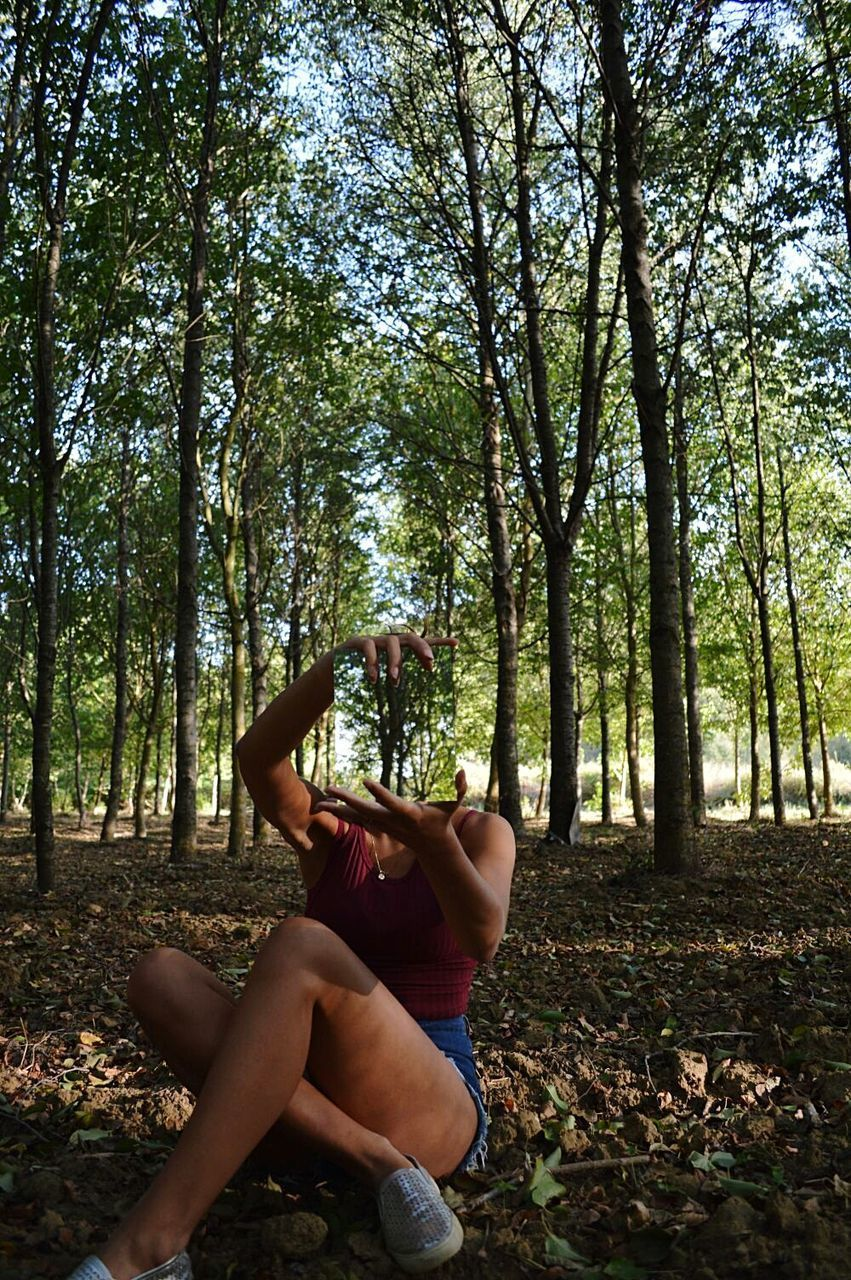 tree, forest, full length, nature, one person, day, young adult, young women, leisure activity, tranquility, beauty in nature, tree trunk, real people, outdoors, sitting, lifestyles, branch, growth, people