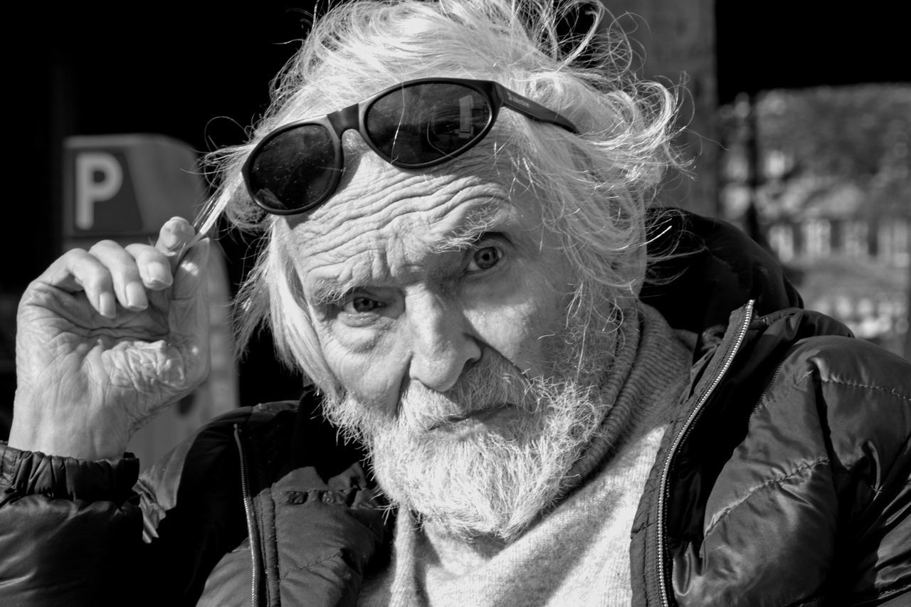 real people, senior adult, one person, leisure activity, sunglasses, front view, lifestyles, bad habit, beard, senior men, casual clothing, looking at camera, addiction, portrait, social issues, headshot, outdoors, day, close-up, people