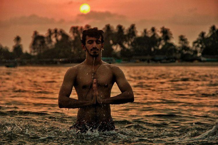 Shirtless Man Standing In Praying Position During Sunrise On Water