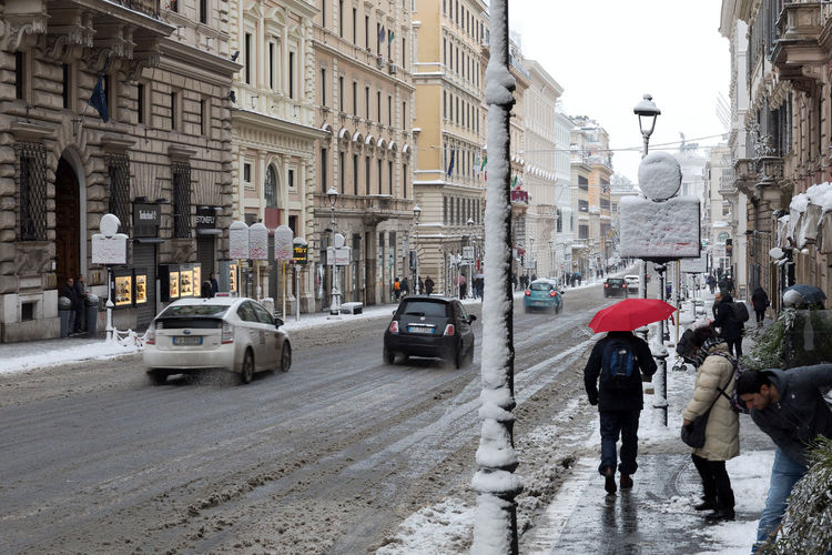 Rome, Italy - February 26, 2018: An exceptional weather event causes a cold and cold air across Europe, including Italy. Snow comes in the capital, covering streets and monuments of a white white coat. In the photo Via Nazionale. City Ice Rome Winter Wintertime Architecture Building Exterior Built Structure Car City Day Italy Land Vehicle Lifestyles Outdoors People Polaroid Real People Snow Snowing Street Streetphotography Transportation Urban Walking