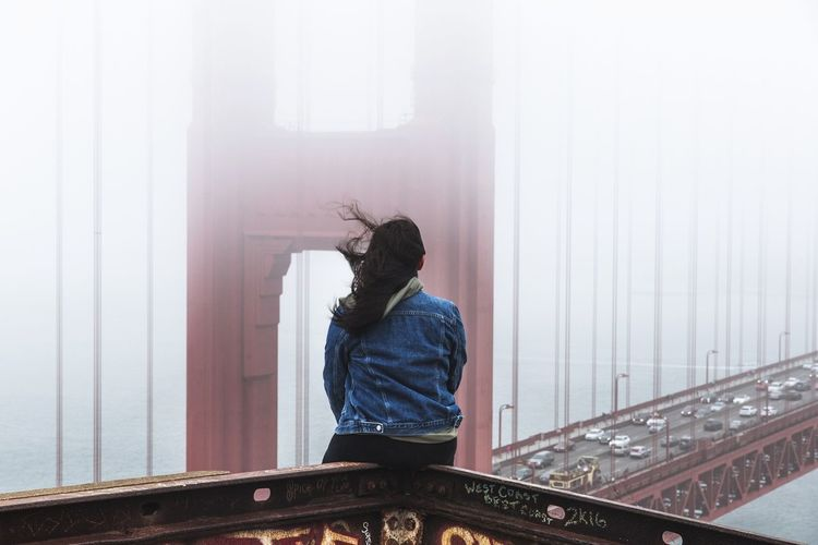 Rear view of woman sitting on railing against bridge during foggy weather
