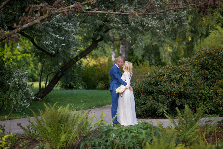 Side view of wedding couple kissing while standing on footpath amidst plants at park