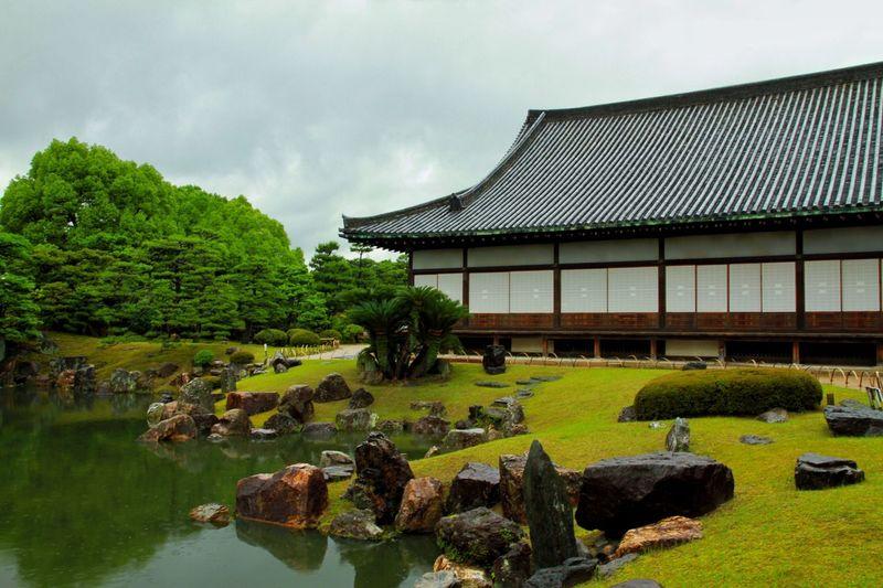 Nijo castle by pond against sky