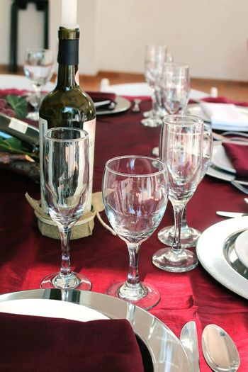 Close-up of wine bottles amidst glasses on table