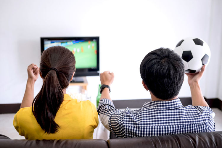 Rear View Of Man And Woman Watching On Soccer At Home