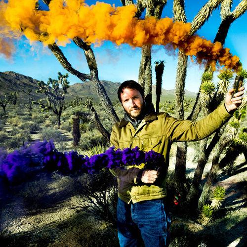 Portrait of man holding smoke bomb at field