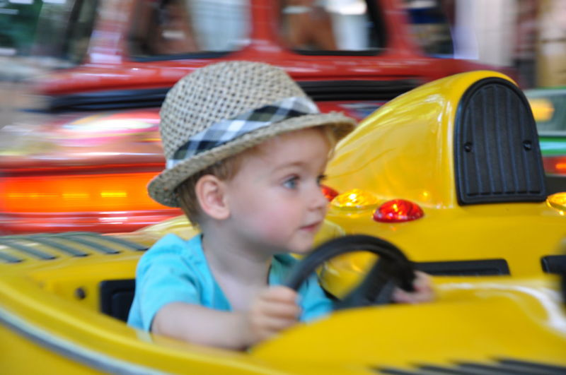 Boy enjoying bumper car ride at amusement park