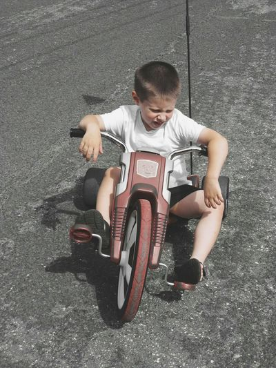 Up Close Street Photography Children Child's Imagination Ride Ride Or Die Rest Autistic Child Autistic Boy Child Racing Big Wheel Vintage Vintage Bicycles Vintage Toys Baby J Autistic Riding Childhood Child At Play Children At Play Boy Riding Big Wheel Need For Speed Autism Imagination The Essence Of Summer