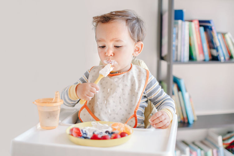 Baby boy eating ripe berries and fruits with yogurt. supplementary healthy food for toddlers kids.