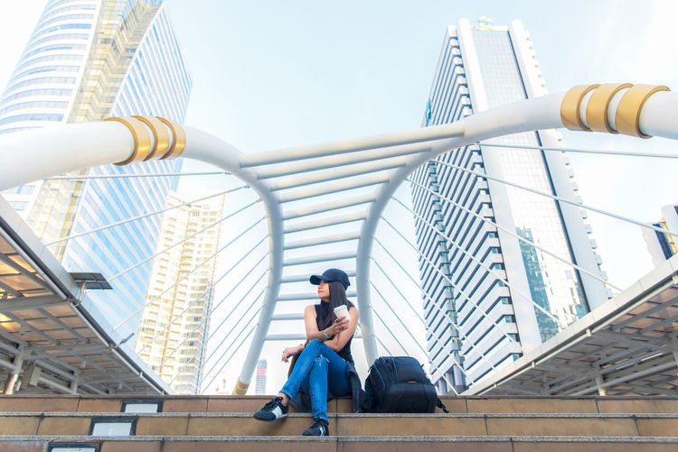 Low angle view of man sitting on bridge against sky