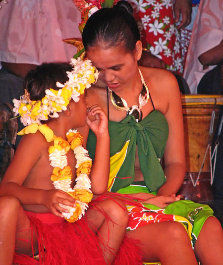 French Polynesian Touristic Cultural Show with local musicians and adult female dancers with family children- Island of Tahitti, French Polynesia Elder Sister French Polynesia Small Talk Tahiti ❤ Beautiful Woman Bonding Boy Wearing Skirt Bride Celebration Confidential Chit Chat Day Flower Front View Groom Happiness Leisure Activity Life Events Lifestyles Outdoors Real People Red Grass Skirt Sari Sitting Tahitian Dancers Three Quarter Length Togetherness Traditional Clothing Two People Wedding Wedding Dress Young Adult Young Women