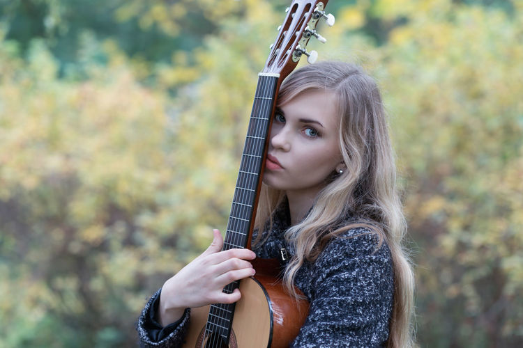 Portrait of beautiful young woman holding guitar outdoors