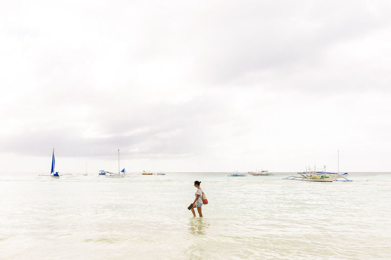 A lone young female walking through a empty sea with Filipino boats on the white horizon. Boracay Filipino Philippines Across Alone Beach Blanched Boats Bright Clouds Empty Female Fishing Boats Sea Single Wading Walking White Woman Young Water Sky Nautical Vessel Transportation Real People One Person Day Mode Of Transportation Lifestyles Land Nature Beauty In Nature Leisure Activity Scenics - Nature Full Length Rear View Shirtless Sailboat Outdoors Horizon Over Water