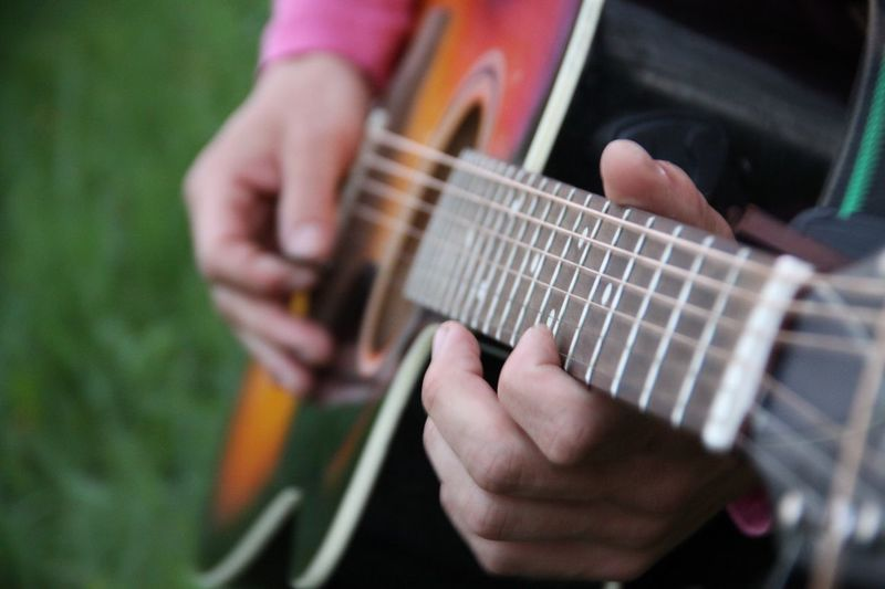 Close-up mid section of a man playing guitar