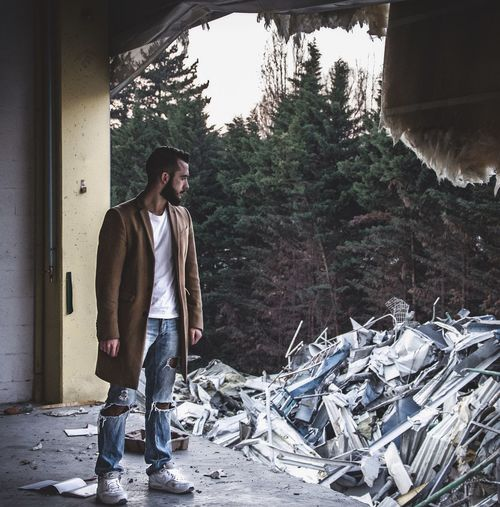 Young man standing at abandoned factory