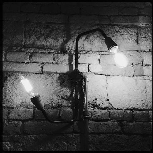 Lamp post against brick wall