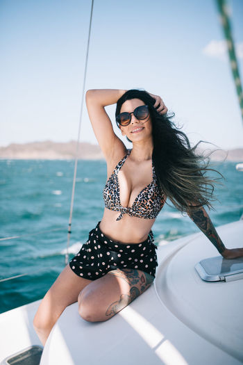 Young woman wearing sunglasses sitting on boat against sea