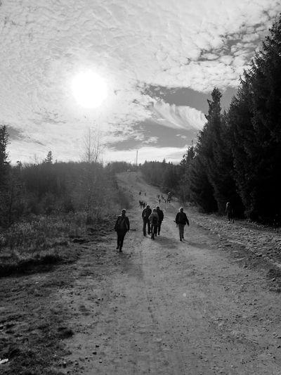 Rear view of people walking on field against sky