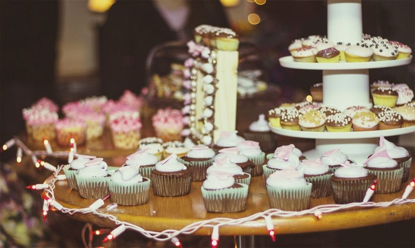 Various cupcakes arranged on stands at restaurant