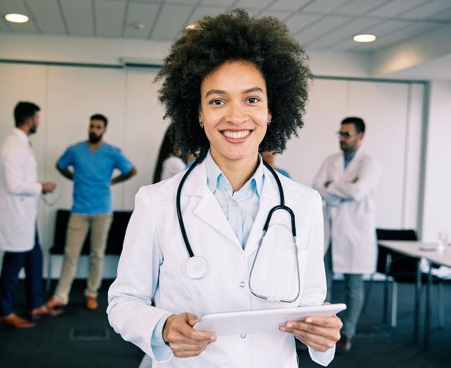 Portrait of smiling female doctor holding digital tablet