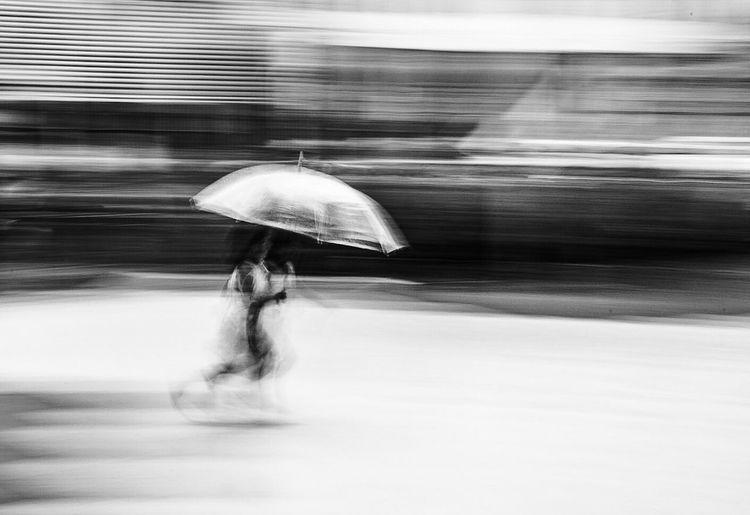Blurred motion of man walking in rain