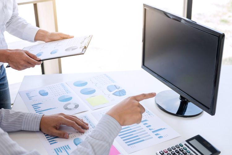 Midsection of businessman and colleague working over graph on table