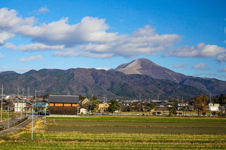 Scenic view of field by houses and mountains against sky