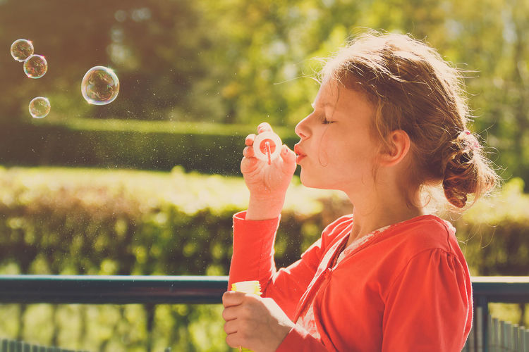 Close-up of girl blowing bubbles at park