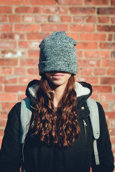 Brick Wall Casual Clothing Close-up Day Front View Jacket Knit Hat Leisure Activity Lifestyles Medium-length Hair One Person Outdoors Real People Standing Warm Clothing Women Young Adult Young Women